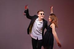 Couples heureux tenant la bouteille de champagne et de danse Photographie stock libre de droits