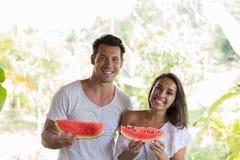 Couples heureux tenant la tranche de pastèque dans des mains étreinte de sourire gaie d'homme et de femme avec la pastèque dehors Images libres de droits