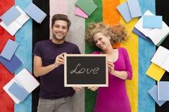 Couples heureux tenant le balcboard avec le mot de ` d'amour de ` Image stock