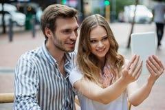 Couples heureux tenant le comprimé numérique tout en se reposant au café de trottoir Image libre de droits