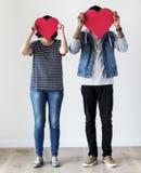 Couples heureux tenant les icônes rouges de coeur Images libres de droits