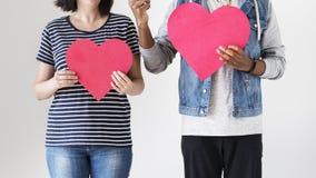 Couples heureux tenant les icônes rouges de coeur Photos stock