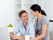 Couples heureux travaillant sur leur ordinateur portatif Photos stock