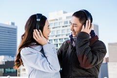 Couples heureux utilisant des écouteurs Image stock