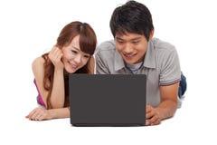 Couples heureux utilisant l'ordinateur portable Photos stock