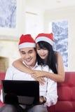 Couples heureux utilisant l'ordinateur portable pour l'achat en ligne Photographie stock libre de droits
