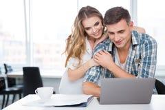 Couples heureux utilisant l'ordinateur portable se reposant ensemble à la table Photographie stock libre de droits