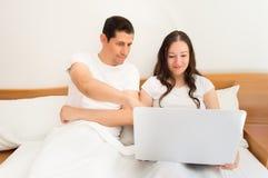 Couples heureux utilisant l'ordinateur portable sur le lit Image stock