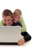 Couples heureux utilisant l'ordinateur portatif Image stock