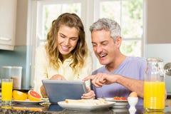 Couples heureux utilisant le comprimé et le petit déjeuner de avoir Image libre de droits