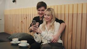 Couples heureux utilisant le smartphone ensemble et riant en café Photos stock