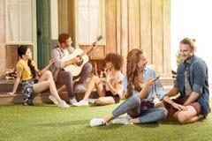 Couples heureux utilisant le smartphone tandis que leurs amis jouant la guitare derrière Images stock