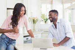 Couples heureux utilisant leur ordinateur portable au petit déjeuner photo libre de droits