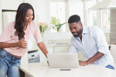 Couples heureux utilisant leur ordinateur portable au petit déjeuner Images stock