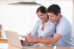Couples heureux utilisant un carnet Image libre de droits