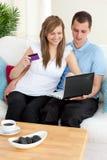 Couples heureux utilisant un ordinateur portatif à acheter en ligne Photographie stock libre de droits
