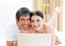 Couples heureux utilisant un ordinateur portatif Photo libre de droits