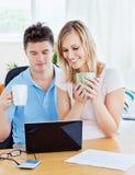 Couples heureux utilisant un ordinateur portatif se reposant ensemble Image libre de droits