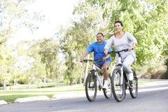 Couples hispaniques aînés faisant un cycle en stationnement Images stock