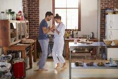 Couples hispaniques dans des pyjamas dansant dans la cuisine, intégrale Images libres de droits