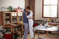 Couples hispaniques dans des pyjamas embrassant dans la cuisine Images libres de droits