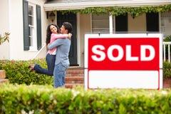 Couples hispaniques en dehors de maison avec le signe vendu Photographie stock libre de droits