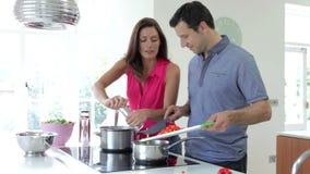 Couples hispaniques faisant cuire le repas à la maison banque de vidéos