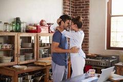 Couples hispaniques heureux embrassant dans la cuisine pendant le matin Photographie stock