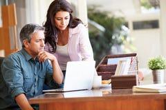 Couples hispaniques inquiétés utilisant l'ordinateur portable sur le bureau à la maison image stock