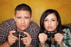 Couples hispaniques jouant le jeu vidéo photos stock