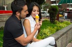 Couples hispaniques mignons partageant le cornet de crème glacée et Images stock