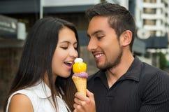 Couples hispaniques mignons partageant le cornet de crème glacée et Image libre de droits