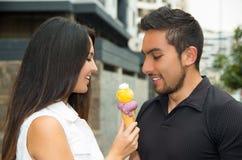 Couples hispaniques mignons partageant le cornet de crème glacée et Photographie stock