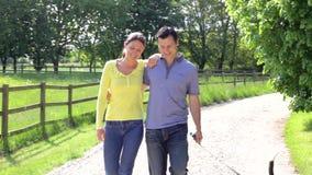 Couples hispaniques prenant le chien pour la promenade dans la campagne banque de vidéos