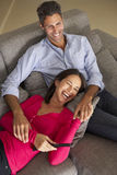 Couples hispaniques sur Sofa Watching TV Image stock
