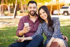 Couples hispaniques utilisant des smartphones Photographie stock