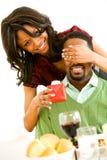 Couples : Homme de Suprises de femme avec le présent au dîner Photo stock