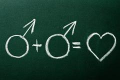 Couples homosexuels dans des symboles d'amour Photographie stock