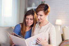 Couples homosexuels des femmes lesbiennes à la maison sur l'observation de divan Image stock