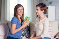 Couples homosexuels des femmes lesbiennes à la maison sur le celebrat de divan Photo stock