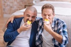 Couples homosexuels positifs mangeant le gâteau ensemble Photographie stock libre de droits
