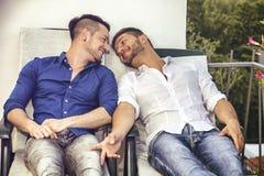 Couples homosexuels sur des chaises au balcon Photographie stock libre de droits