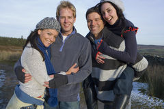 Couples hugging in rural field.  stock image