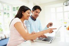 Couples indiens faisant l'achat en ligne à la maison Photo stock