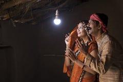 Couples indiens ruraux ravis sur l'électricité atteignant leur maison images libres de droits