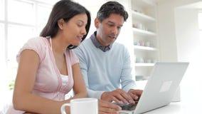 Couples indiens utilisant l'ordinateur portable dans la cuisine à la maison banque de vidéos