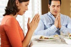 Couples indiquant la grâce avant repas à la maison Images stock