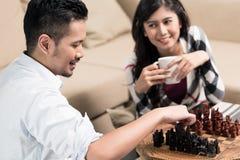 Couples indonésiens jouant des échecs à la maison Images stock