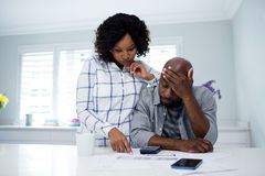 Couples inquiétés agissant l'un sur l'autre tout en vérifiant les factures photographie stock