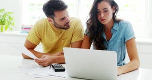 Couples inquiétés calculant leurs factures avec l'ordinateur portable dans la cuisine banque de vidéos